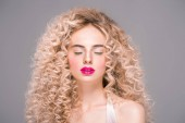 beautiful young woman with long curly hair standing with closed eyes isolated on grey