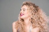 happy young woman with long curly hair laughing isolated on grey