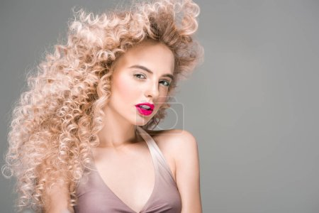 Photo for Portrait of beautiful young woman with long curly hair looking at camera isolated on grey - Royalty Free Image