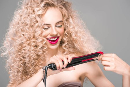 smiling young woman with long curly hair holding hair straightener isolated on grey