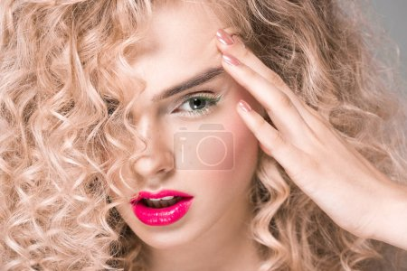 Photo for Close-up portrait of beautiful young woman with long curly hair looking at camera on grey - Royalty Free Image