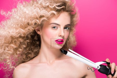 beautiful naked girl with long curly hair holding hair curler and looking at camera isolated on pink
