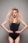 beautiful young woman with long curly hair standing with hands on waist and looking at camera on grey