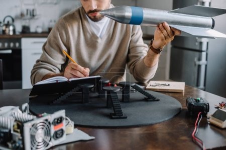 Photo for Cropped image of engineer holding rocket model and making notes at home - Royalty Free Image