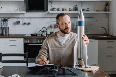 handsome engineer looking at rocket model and making notes at home
