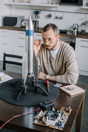 handsome engineer looking above glasses at rocket model at home