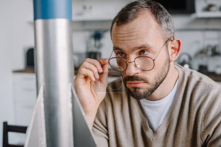 portrait of handsome engineer looking above glasses at rocket model at home