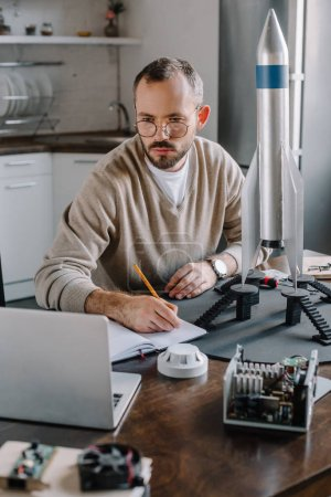 handsome engineer modeling rocket, looking at laptop and making notes at home