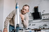 handsome engineer modeling rocket and measuring with ruler at home
