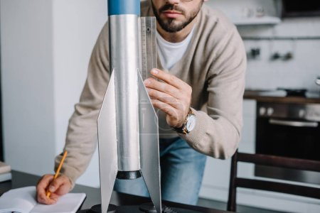 cropped image of engineer modeling rocket and measuring with ruler at home