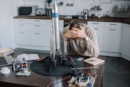 exhausted engineer sitting at table with rocket model at home