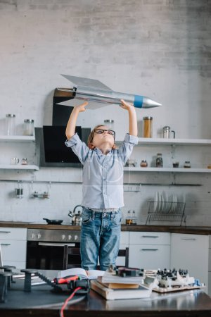 adorable boy holding rocket model in kitchen on weekend