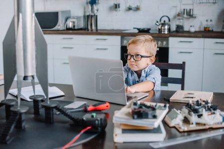 Photo pour Drôle adorable garçon en utilisant ordinateur portable à la table avec modèle de fusée dans la cuisine le week-end - image libre de droit