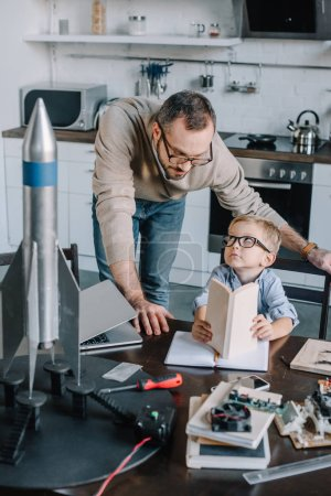 Photo for Father and son modeling rocket and looking at each other at home - Royalty Free Image
