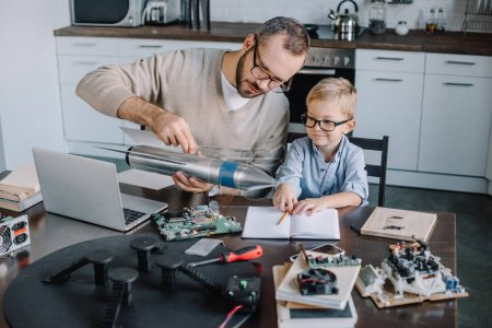 father and son testing rocket model together at home