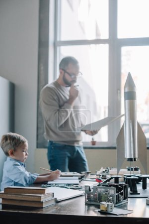 pensive father and son modeling rocket at home