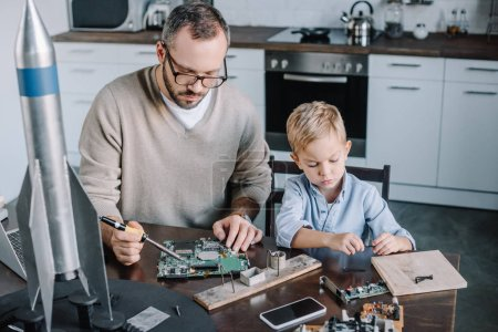 father and son soldering circuit board with soldering iron in kitchen