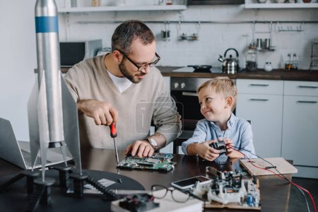 Photo for Cheerful father and son repairing circuit board and looking at each other at home - Royalty Free Image
