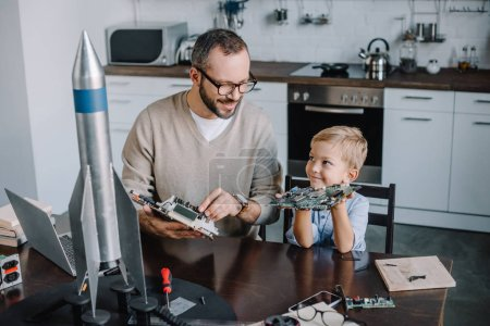 father and son repairing circuit board and looking at each other at home
