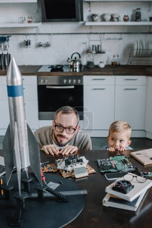 father and son looking out from table in kitchen and looking at rocket model
