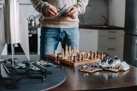 cropped image of man standing near table with chess board and holding glasses at home