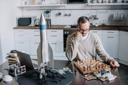 Photo for Pensive handsome man looking at chess board at home - Royalty Free Image