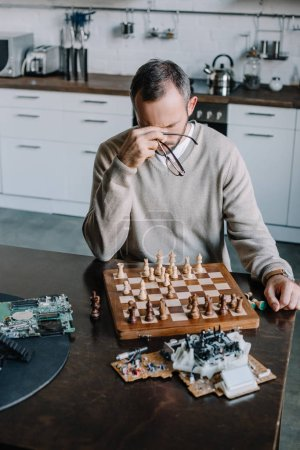 Photo for High angle view of tired man playing chess and touching nose bridge at home - Royalty Free Image