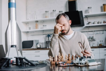Photo for Tired handsome man playing chess and touching nose bridge at home - Royalty Free Image