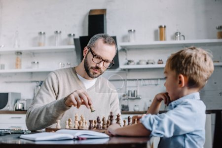 father and adorable little son playing chess together at home