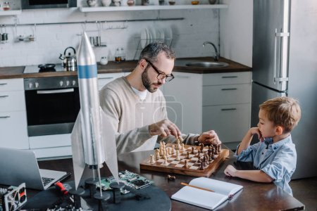 father and cute little son playing chess together at home