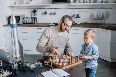 high angle view of father teaching little son playing chess