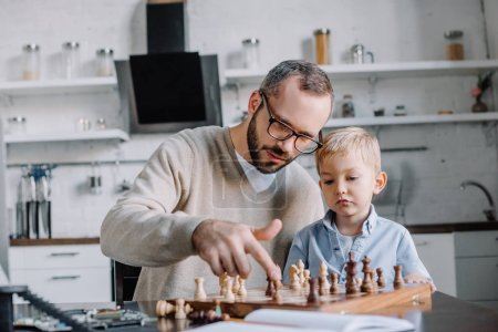 father teaching little son playing chess at home