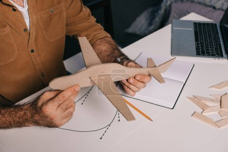 cropped shot of man holding cardboard plane model while modeling at home