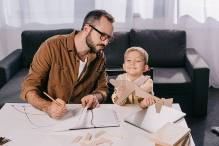 father in eyeglasses and cute little son modeling plane together at home