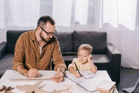 father and little son drawing while modeling plane together at home