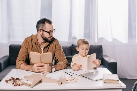 father and little son holding books while modeling plane at home