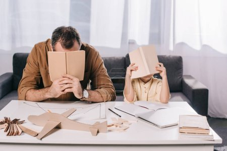 father and son hiding faces behind books while modeling together at home