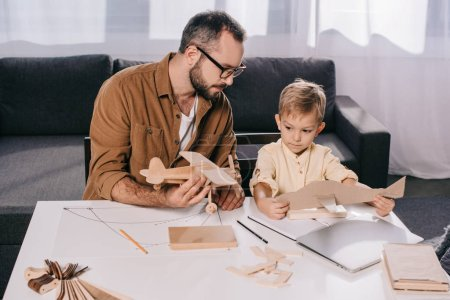 father in eyeglasses and cute little son modeling planes together at home