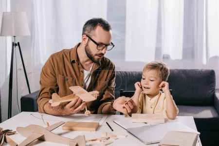 father in eyeglasses and smiling son modeling plane together at home