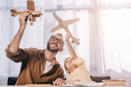 happy father and little son playing with wooden planes models at home