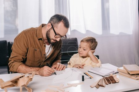 focused father and son modeling wooden plane at home