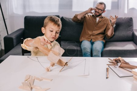 little son playing with wooden plane model while father talking by smartphone behind