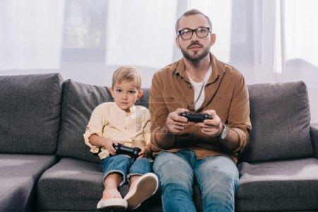 Photo pour Père et petit-petit fils assis sur le canapé et en jouant avec les manettes de jeu - image libre de droit