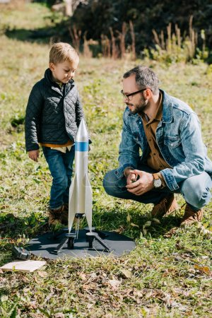 happy father and cute little son playing with model rocket outdoor