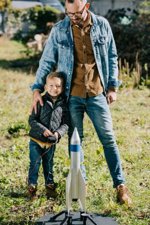 Photo for Happy father with little son smiling at camera while playing with model rocket outdoor - Royalty Free Image