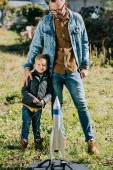 happy father with little son smiling at camera while playing with model rocket outdoor