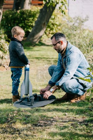 Photo for Side view of father and little son launching model rocket outdoor - Royalty Free Image