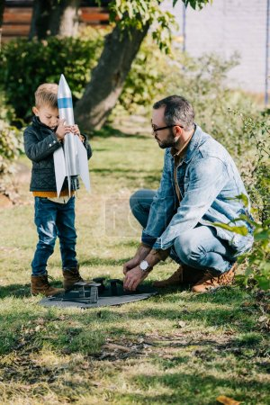 father and son playing with model rocket together at sunny day