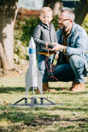 close-up view of model rocket and father with son playing behind