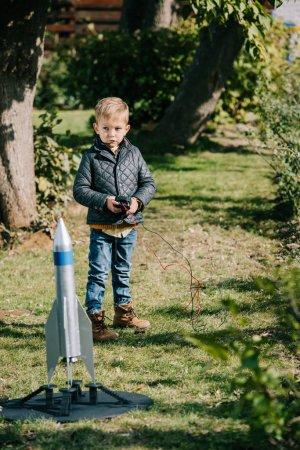 cute little boy launching model rocket outdoor